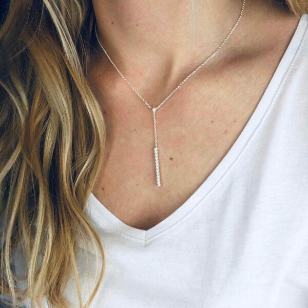 Y Silberkette mit Kugelmuster am Hals einer blonden Frau mit weißem T Shirt
