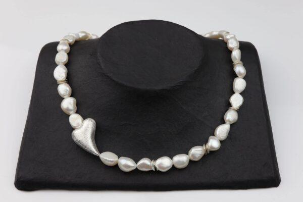 Weiße Perlenkette mit schrägem Silberherz 2x3 cm dazu Silberplättchen und Silberverschluss handgemachtes Unikat auf Pappaufsteller schwarz