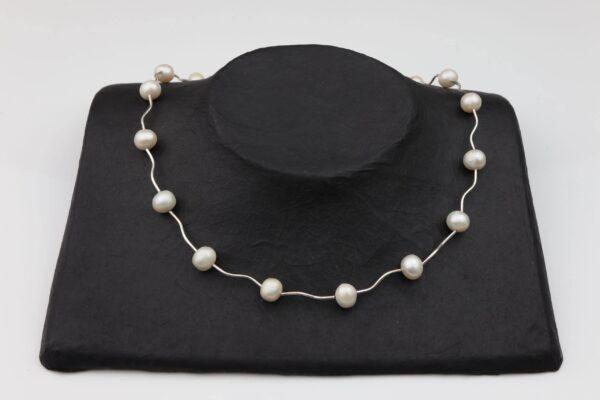 weiße Perlenkette zwischen Silberstäbchen mit Silberverschluss handgemachtes Unikat auf schwarzem Pappaufsteller