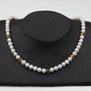 weiße Perlenkette mit kleinen Goldspiralen Silber vergoldet handgemachtes Unikat auf schwarzem Pappaufsteller